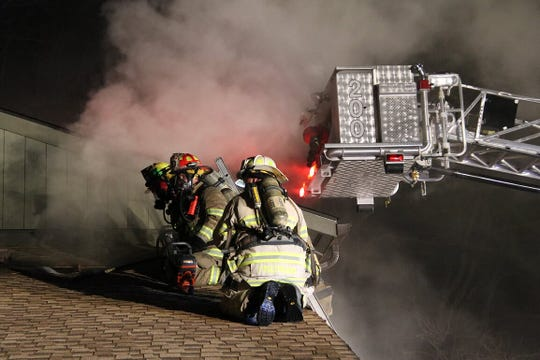 Firefighters in Middletown battle a Saturday night blaze on the roof of a home at Shadow Lake Village, an age-restricted community on the Navesink River.
