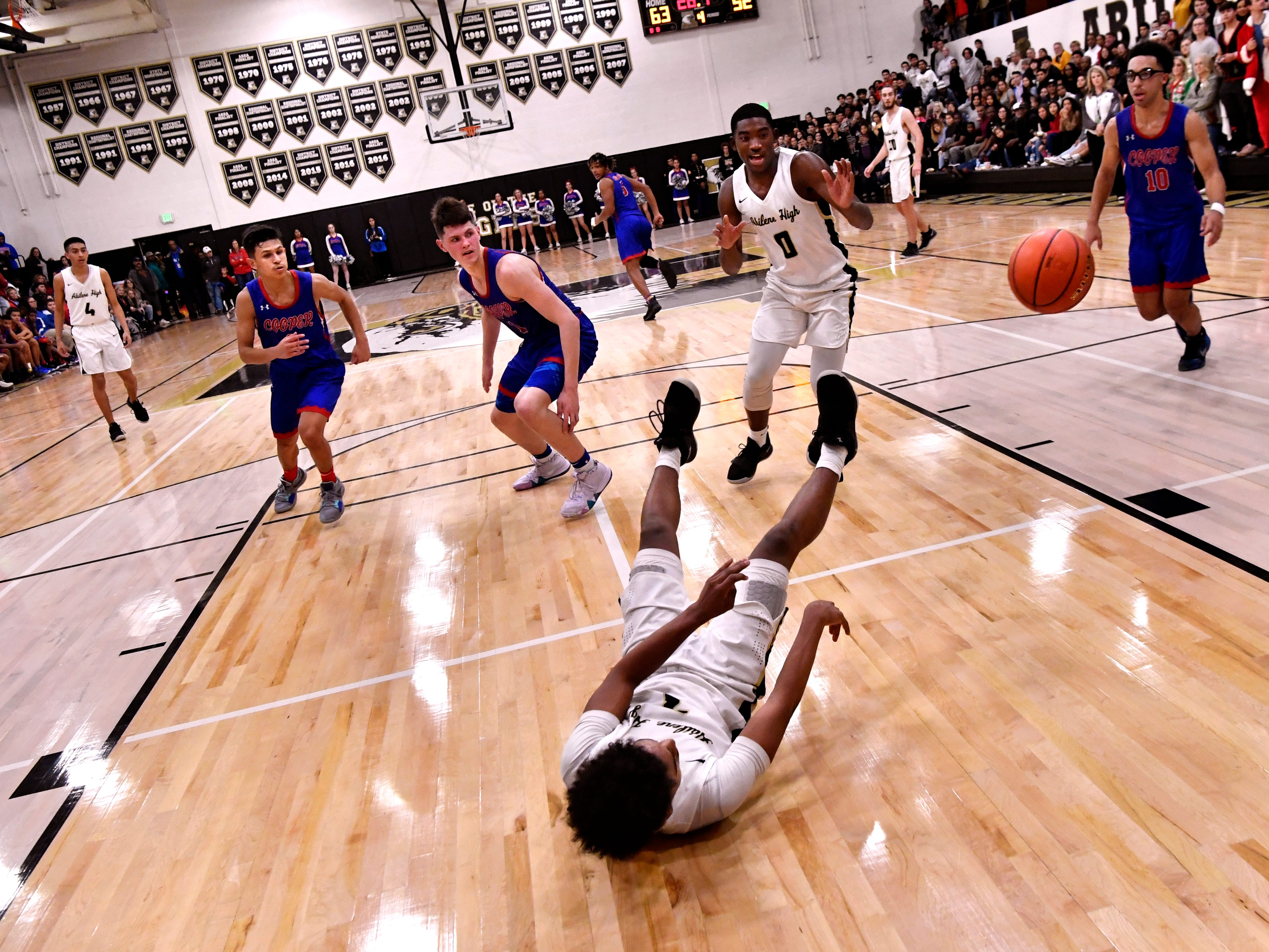 Eagle guard Jalen McGee passes the ball to the right off-camera as he falls to the court floor during Abilene High's crosstown basketball game against Cooper Friday Dec. 14, 2018. Final score was 63-52, Abilene High.