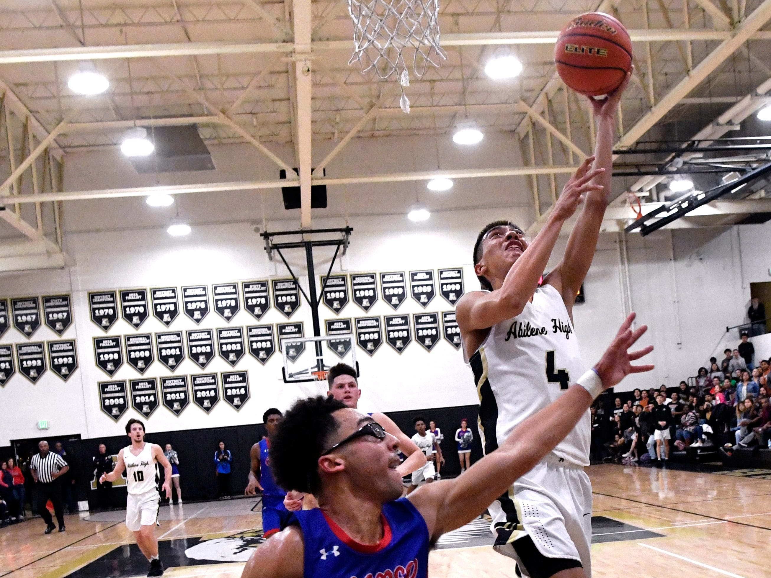 Eagles guard Jojo Escobedo goes for a layup over Cooper guard Ben Thompson during Friday's crosstown basketball game at Eagle Gym Dec. 14, 2018. Final score was 63-52, Abilene High.