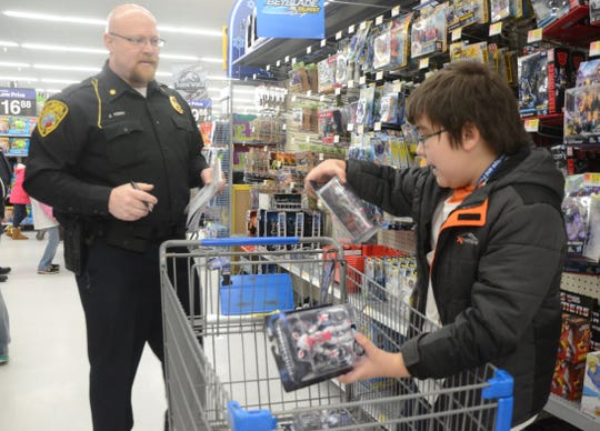 Deputy Chief Jason Kern of the Albion Department of Public Safety, holding the list, shops with Fletcher Gordon, 10.