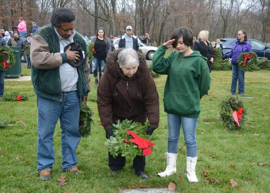 Al Whitfield, his wife, Norris and granddaughter, Katherine, place a wreath at Fort Custer National Cemetery on Saturday.