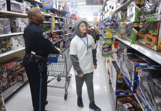 Marshall Officer Jeshua Whitley shops the toy section with Sean Dixon, 12.