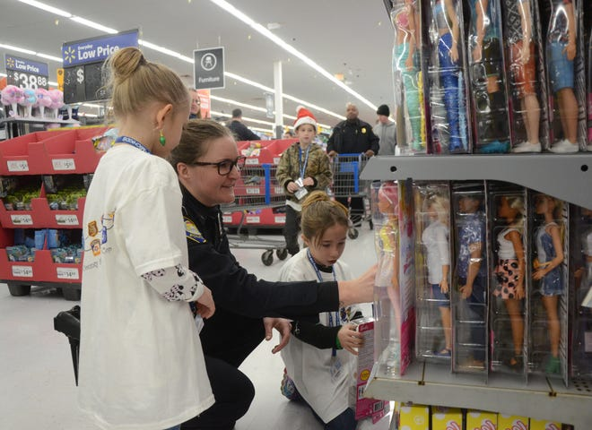 Battle Creek Police Officer Emily Leach helps cousins, Amilyah Pejakovich, 6, left, and Rylegh Baker, 8, shop for dolls.