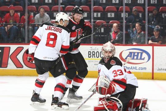 Binghamton Devils goalie Cam Johnson looks left as teammate Josh Jacobs defends during Saturday's game at Floyd L. Maines Veterans Memorial Arena. Binghamton won, 3-1.