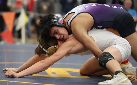 North Kitsap's Robert Gomez (top) grapples with Puyallup's Cody Bolstad during their 132-pound bout for the finals of the HammerHead Invitational Wrestling Tournament at the Kitsap Sun Pavilion on Saturday, December 15, 2018.