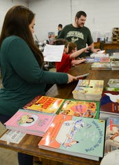 Volunteers pick out toys and books at last year's Reaching Out Toy Drive distribution day.