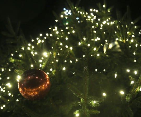 Giant ornaments hang off a Christmas tree.