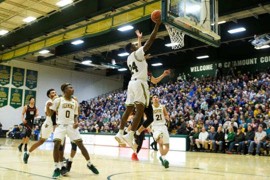 Vermont guard Ben Shungu (24) leaps for a lay up during the men's basketball game between the Northeastern Huskies and the Vermont Catamounts at Patrick Gym on Sunday afternoon December 16, 2018 in Burlington.