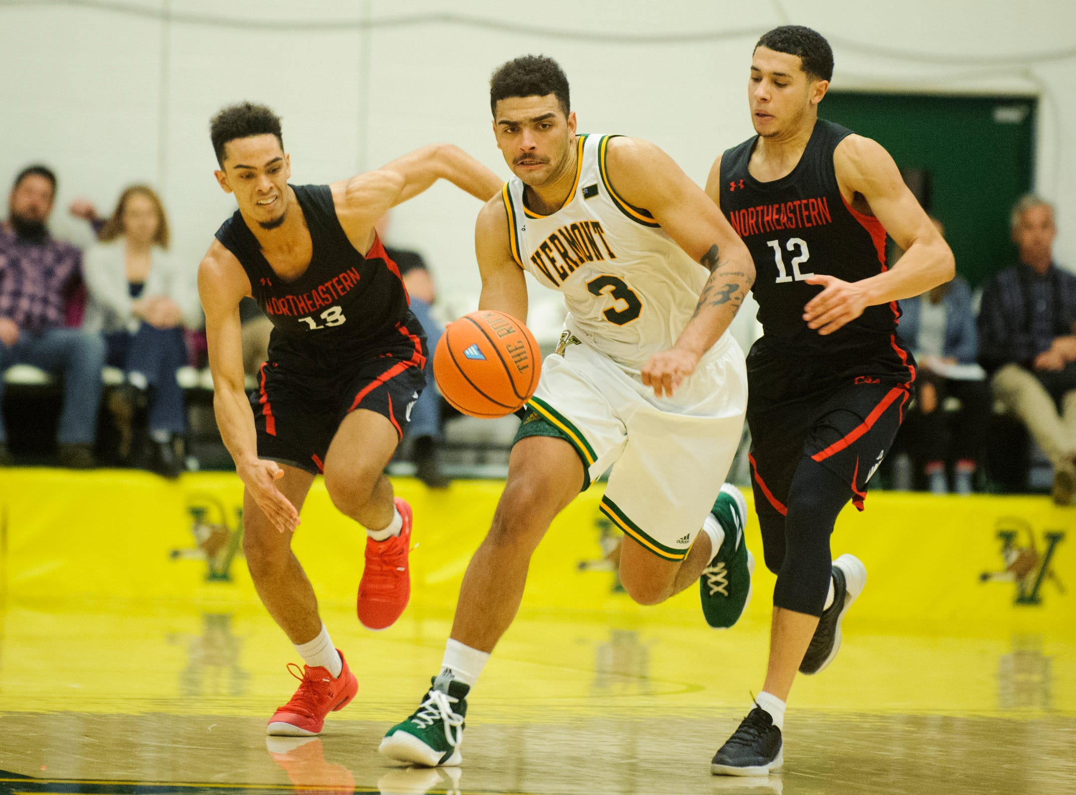 Vermont forward Anthony Lamb (3) runs down the court with the ball past Northeastern's Jordan Roland (12) and Myles Franklin (13) during the men's basketball game between the Northeastern Huskies and the Vermont Catamounts at Patrick Gym on Sunday afternoon December 16, 2018 in Burlington.