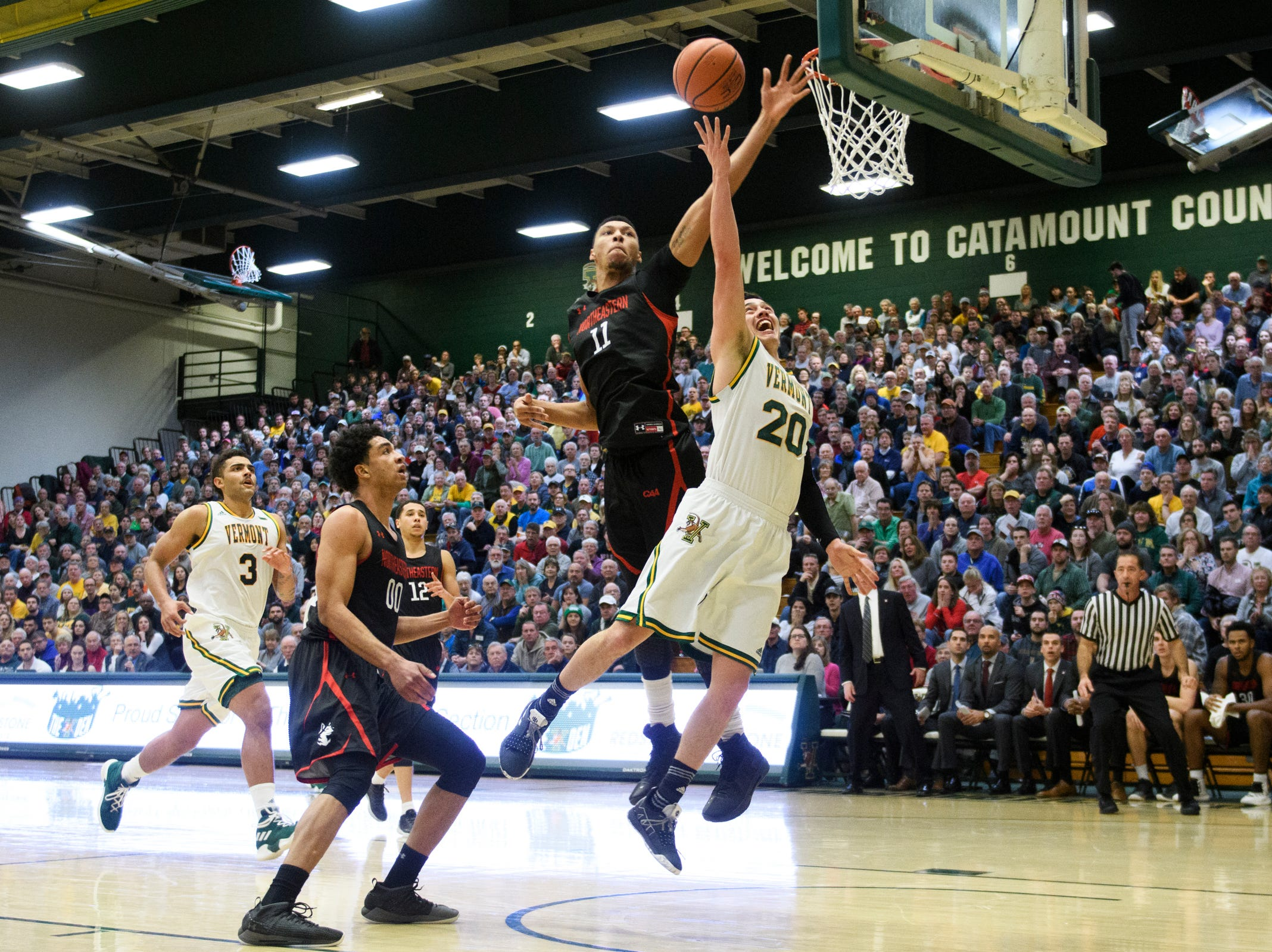 Vermont guard Ernie Duncan (20) leaps to shoot a lay up over Northeastern's Jeremy Miller (11) during the men's basketball game between the Northeastern Huskies and the Vermont Catamounts at Patrick Gym on Sunday afternoon December 16, 2018 in Burlington.