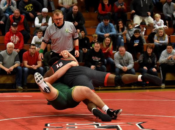 Rob Brown of LaSalle drives Zach Taylor of St. Edward to the mat for a 285lb class pinfall lifting the Lancers to a team dual victory over the Eagles, December 15, 2018.