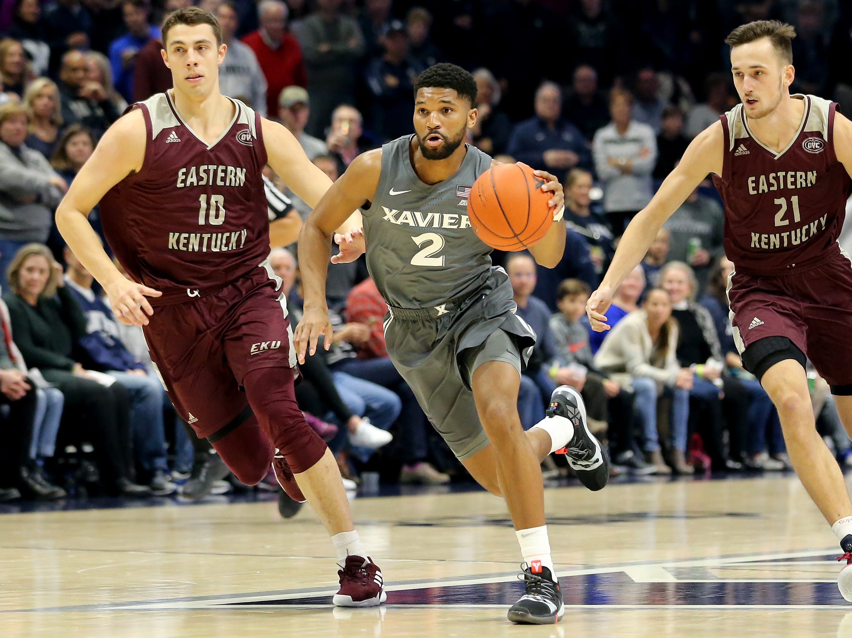 Xavier Musketeers guard Kyle Castlin (2), center, pushes the ball up court as Eastern Kentucky Colonels forward Nick Mayo (10), left, and Eastern Kentucky Colonels forward Lachlan Anderson (21), right, give chase in the first half of an NCAA college basketball game, Saturday, Dec. 15, 2018, at Cintas Center in Cincinnati, Ohio
