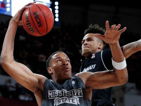 Mississippi State guard Robert Woodard (12) attempts a layup past the defense of Cincinnati guard Cane Broome (15) during the first half of an NCAA college basketball game in Starkville, Miss., Saturday, Dec.15, 2018. (AP Photo/Rogelio V. Solis)