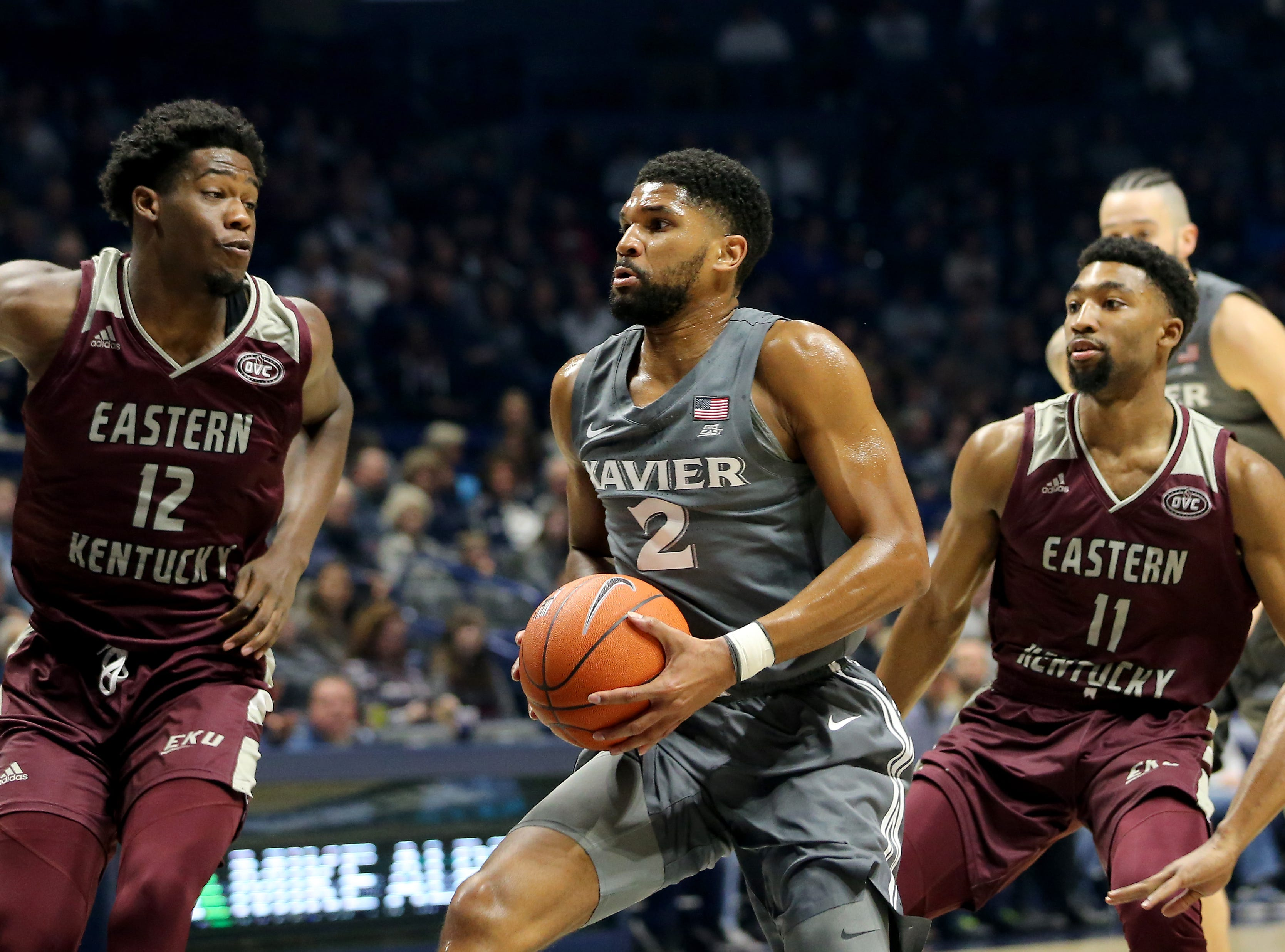 Xavier Musketeers guard Kyle Castlin (2) drives to the basket as Eastern Kentucky Colonels forward Tre King (12), left, and Eastern Kentucky Colonels guard Jomaru Brown (11), right, defend in the first half of an NCAA college basketball game, Saturday, Dec. 15, 2018, at Cintas Center in Cincinnati, Ohio