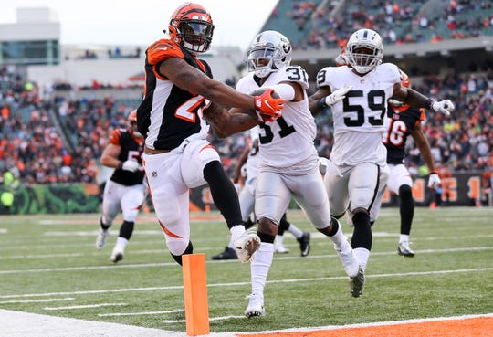 Cincinnati Bengals running back Joe Mixon (28) scores a touchdown as Oakland Raiders strong safety Marcus Gilchrist (31) defends in the fourth quarter of a Week 15 NFL football game, Sunday, Dec. 16, 2018, at Paul Brown Stadium in Cincinnati. The Cincinnati Bengals won 30-16.