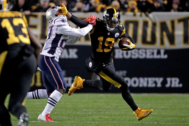 Pittsburgh Steelers wide receiver JuJu Smith-Schuster (19) stiff-arms New England Patriots defensive back J.C. Jackson (27) after catching a pass from quarterback Ben Roethlisberger during the first half of an NFL football game in Pittsburgh, Sunday, Dec. 16, 2018.
