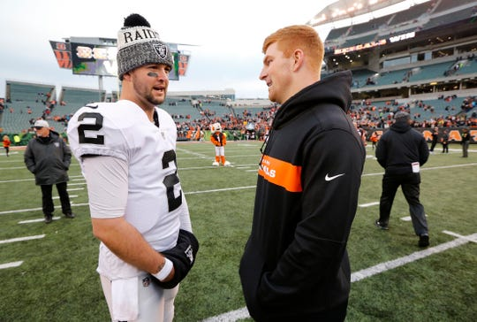 Former Bengals backup quarterback AJ McCarron talks with injured Cincinnati Bengals quarterback Andy Dalton (14) after the fourth quarter of the NFL Week 15 game between the Cincinnati Bengals and the Oakland Raiders at Paul Brown Stadium in downtown Cincinnati on Sunday, Dec. 16, 2018. The Bengals won the final home game of the season, 30-16.