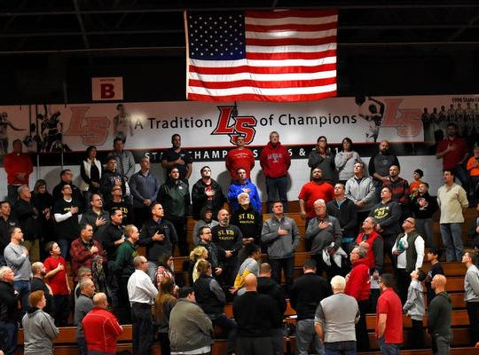Fans from LaSalle and St. Edward look up to the United States Flag with hand on heart to honor America as one during the National Anthem prior to the wrestling dual between the Lancers and the Eagles, December 15, 2018.