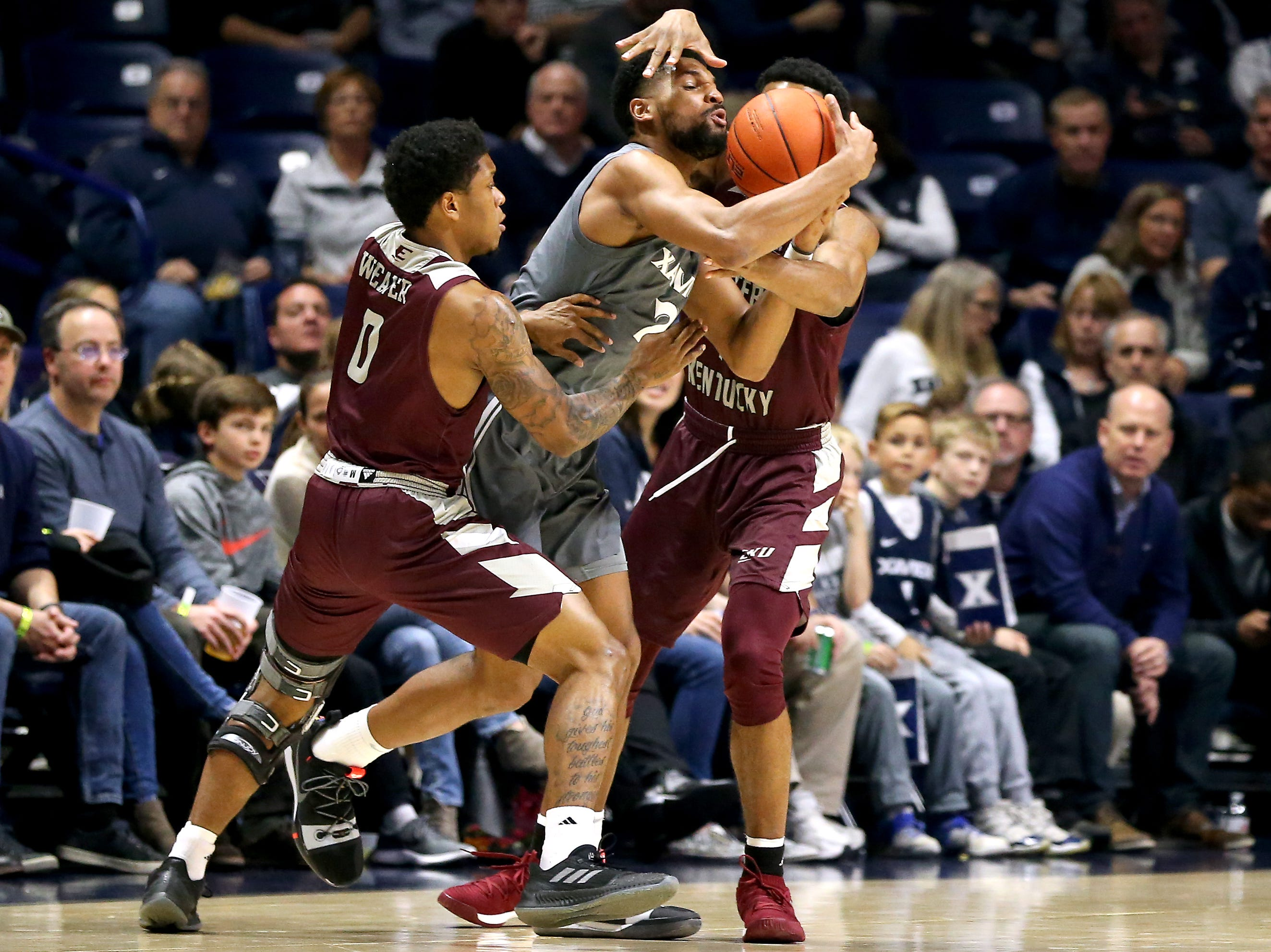 Xavier Musketeers guard Kyle Castlin (2) maintains possession as Eastern Kentucky Colonels guard Dujuanta Weaver (0), left, and Eastern Kentucky Colonels guard Jomaru Brown (11), right, defend in the first half of an NCAA college basketball game, Saturday, Dec. 15, 2018, at Cintas Center in Cincinnati, Ohio