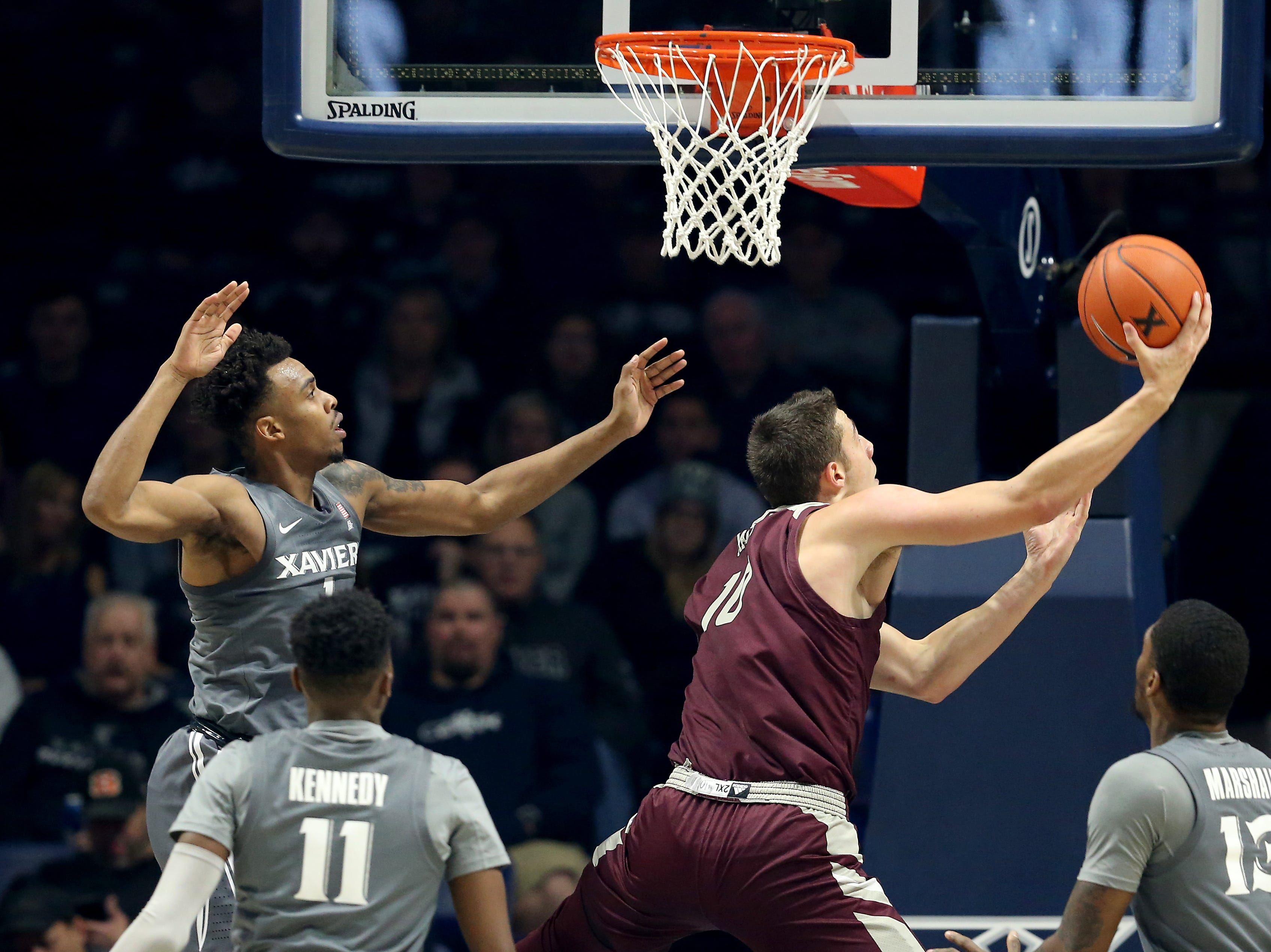 Eastern Kentucky Colonels forward Nick Mayo (10) goes up and under to the basket as Xavier Musketeers guard Paul Scruggs (1) defends in the first half of an NCAA college basketball game, Saturday, Dec. 15, 2018, at Cintas Center in Cincinnati, Ohio