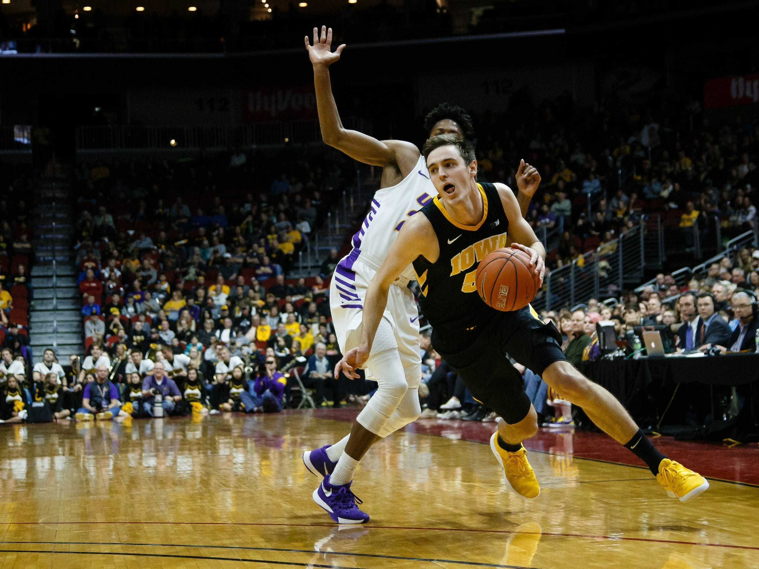 Iowa's Nicholas Baer (51) dribbles around UNI's IsaiahÊBrown (24) during their basketball game at the Hy-Vee Classic on Saturday, Dec. 15, 2018, in Des Moines. Iowa takes a 39-18 lead over UNI into halftime.