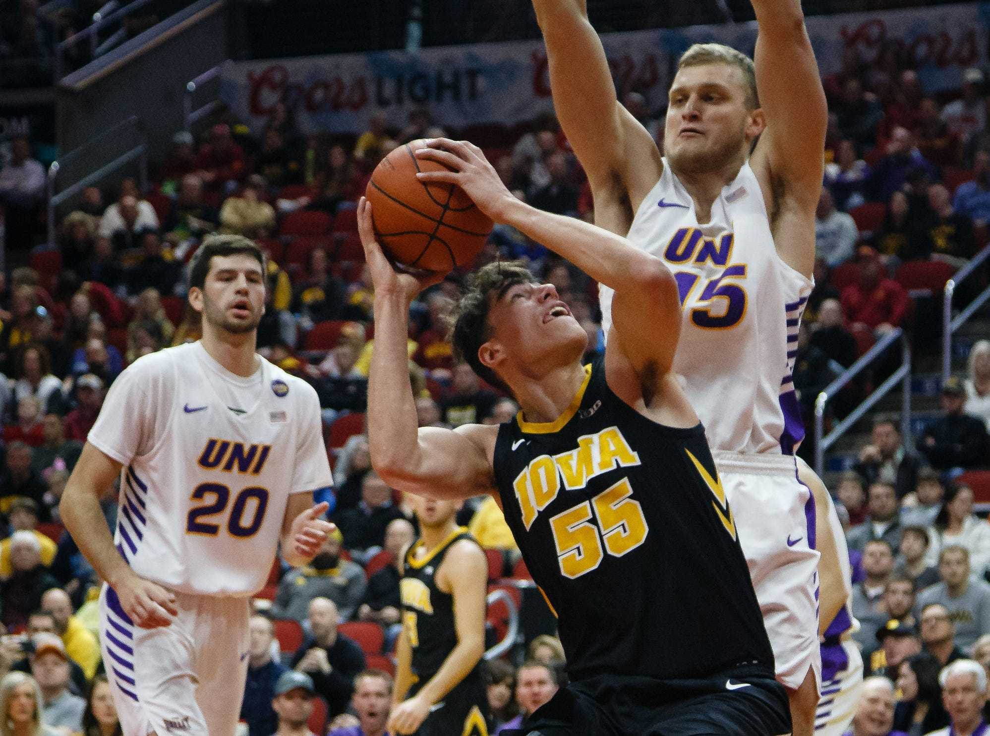 Iowa's Luka Garza (55) tries to get a shot off around UNI's JustinÊDahl (15) during their basketball game at the Hy-Vee Classic on Saturday, Dec. 15, 2018, in Des Moines. Iowa takes a 39-18 lead over UNI into halftime.