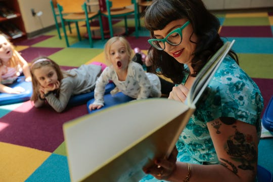 (left to right) Alice Malloure of Huntington Woods, Sydney Marchak of Pleasant Ridge and Olivia Rickard of Huntington Woods react as Children's Librarian Joyce Krom reads the story 'Quick as a Cricket' in 2015 during the weekly pre-school story time at the Huntington Woods Public Library in Huntington Woods.