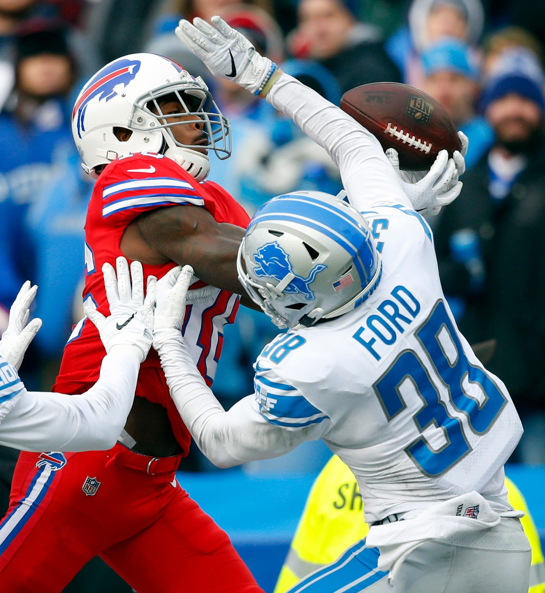 Bills receiver Robert Foster catches a pass under pressure from Lions cornerback Mike Ford during the first half.