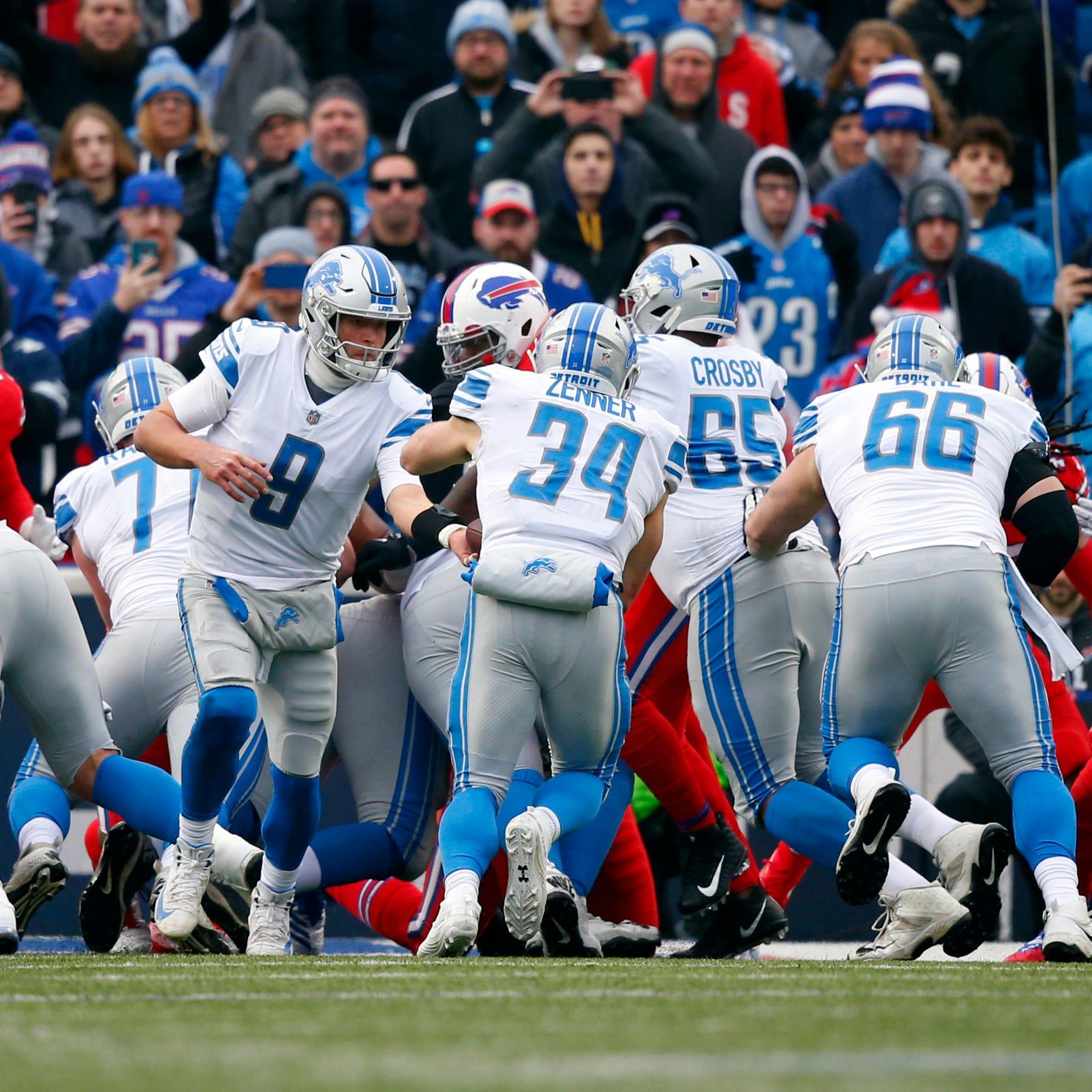Lions quarterback Matthew Stafford hands off the...