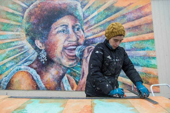 Artist Nicole Macdonald prepares a section of an Aretha Franklin waiting to install on a building on Kercheval Avenue at Alter Road in Detroit on Saturday, Dec. 15, 2018.