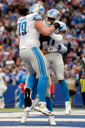 Detroit Lions wide receiver Andy Jones celebrates with guard Kenny Wiggins after catching a 4-yard touchdown pass during the first half.
