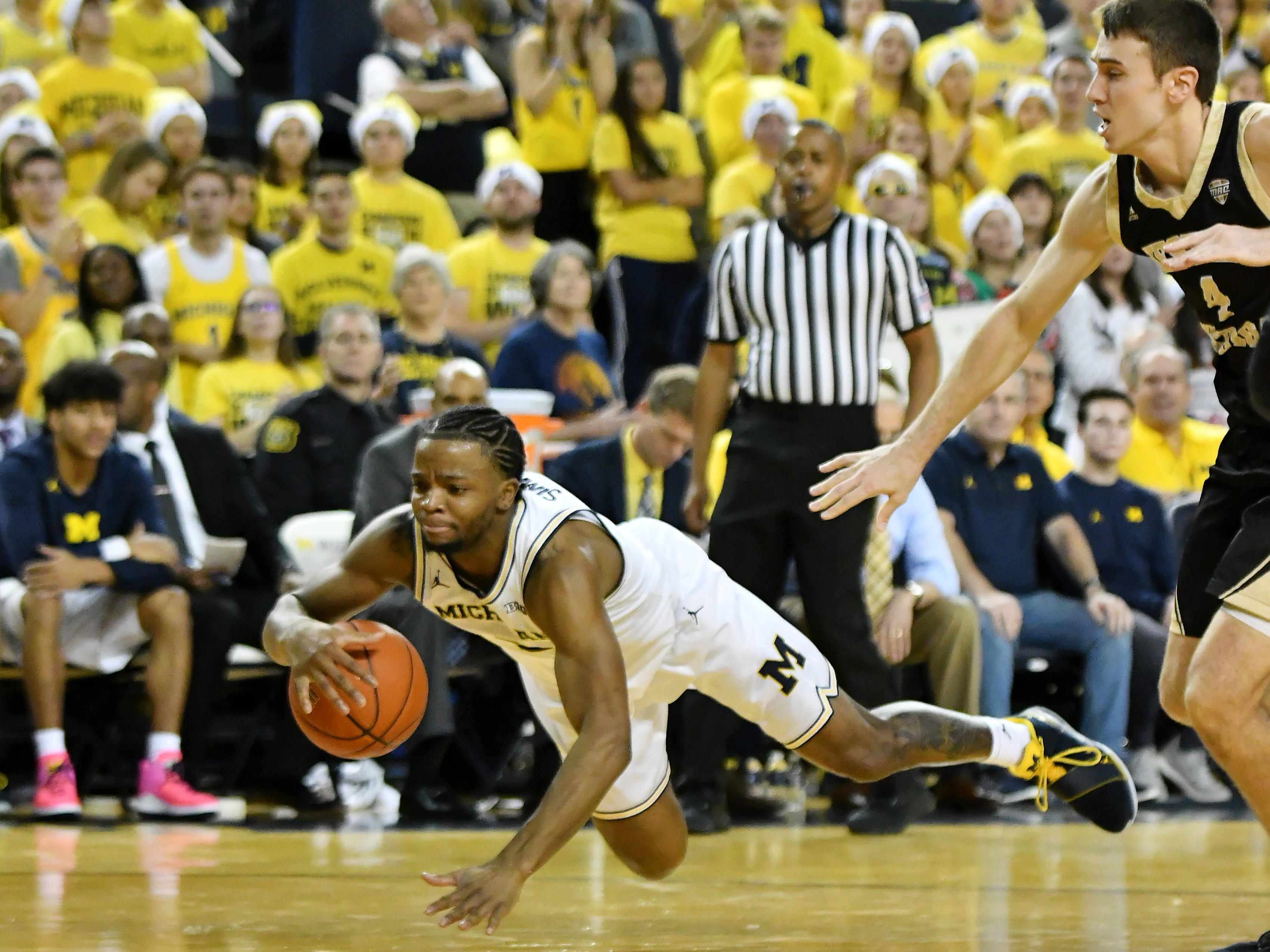 Michigan guard Zavier Simpson (3) goes for a loose ball in front of Western Michigan guard Jared Printy (4) in the second half.