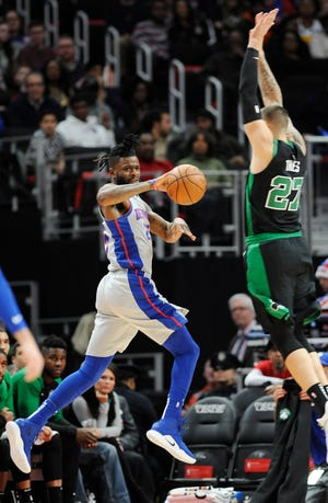 Pistons' Reggie Bullock makes a pass over Celtics' Daniel Theis in the first quarter. Bullock had 15 points and 3 rebounds. The Pistons defeated the Celtics 113-104, Saturday, December 15, 2018 at Little Caesars Arena in Detroit, Michigan.