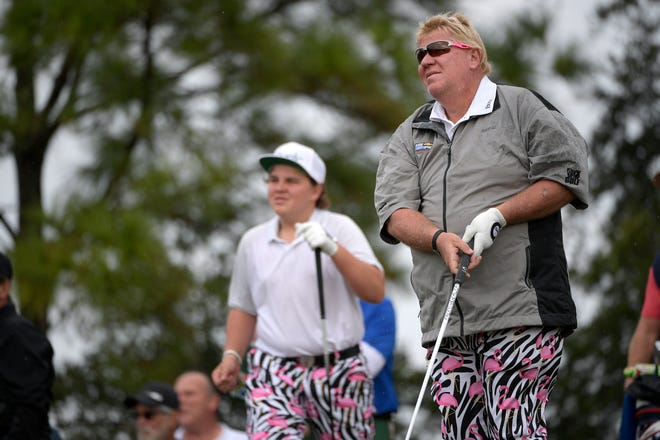 Little John Daly, left, watches the tee shot of his father, John Daly, on the 10th hole.