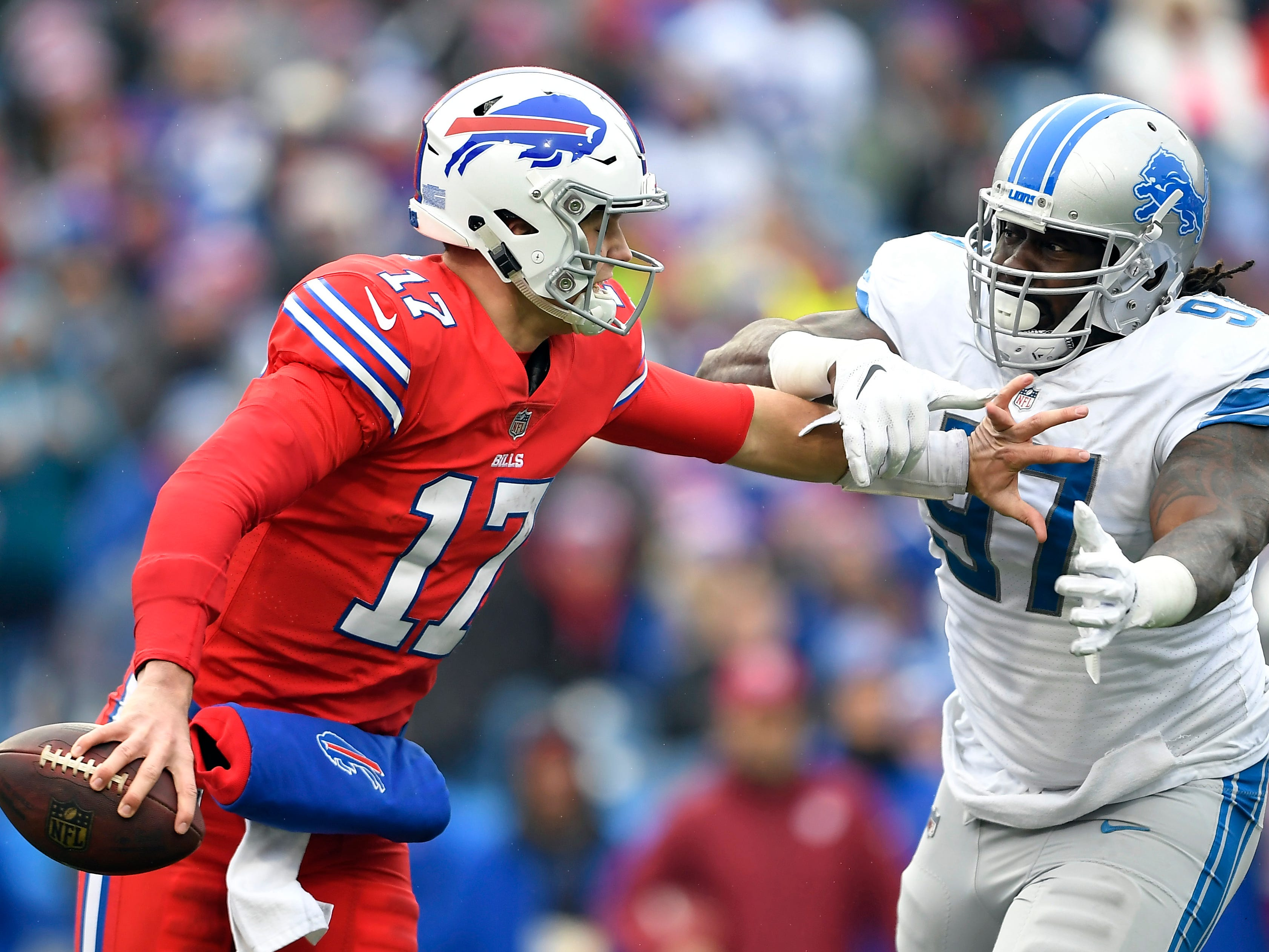 Buffalo Bills quarterback Josh Allen (17) avoids a tackle by Detroit Lions defensive tackle Ricky Jean Francois (97) during the first half.