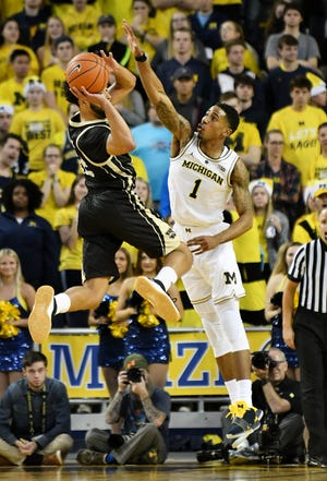 Michigan's Charles Matthews (1) defends Western Michigan guard Michael Flowers during last week's game.