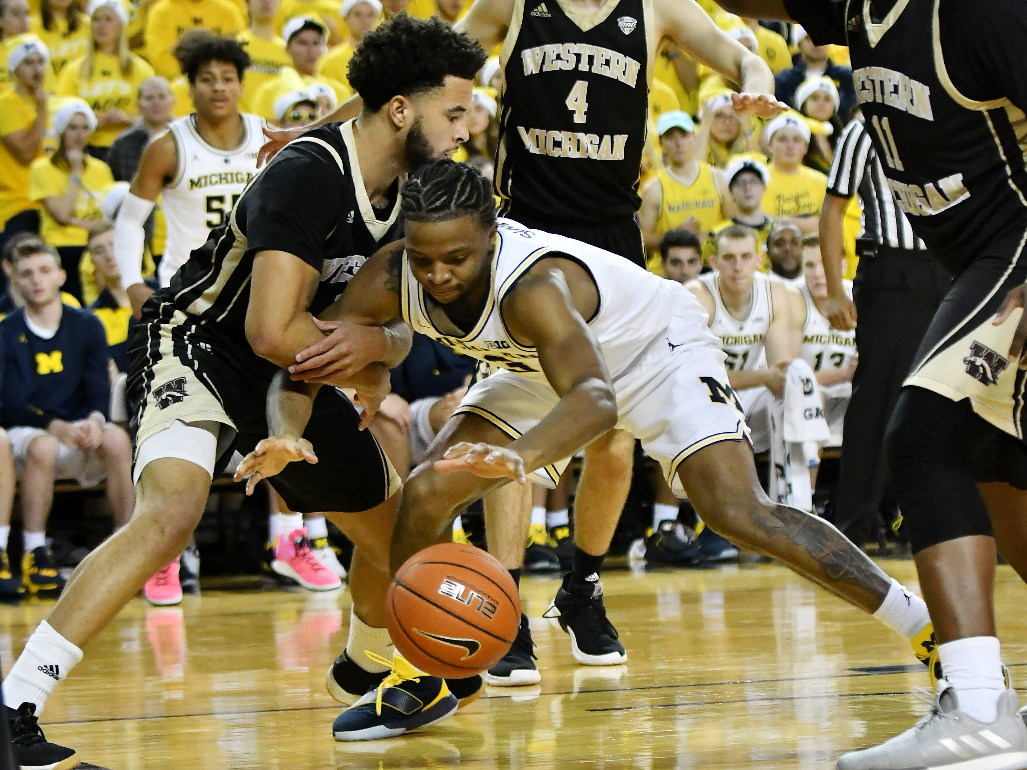 Western Michigan guard Michael Flowers (12) and Michigan guard Zavier Simpson (3) battle for the ball in the second half.