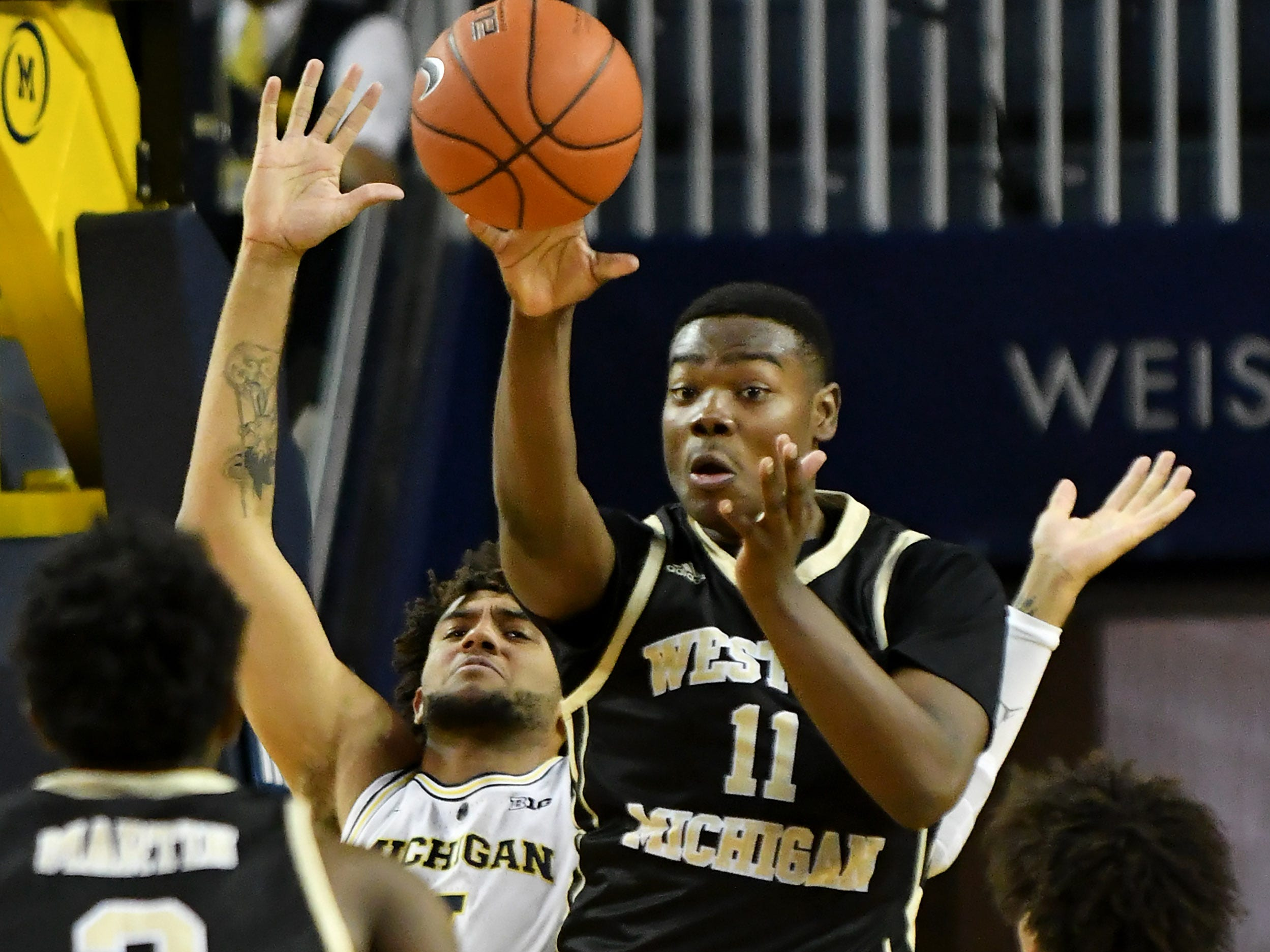 Western Michigan forward Kawanise Wilkins (11) passes the ball away from the defense of Michigan forward Isaiah Livers (4) in the second half.