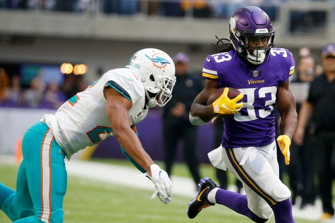Minnesota Vikings running back Dalvin Cook, right, runs from Miami Dolphins strong safety T.J. McDonald during the first half on Sunday.