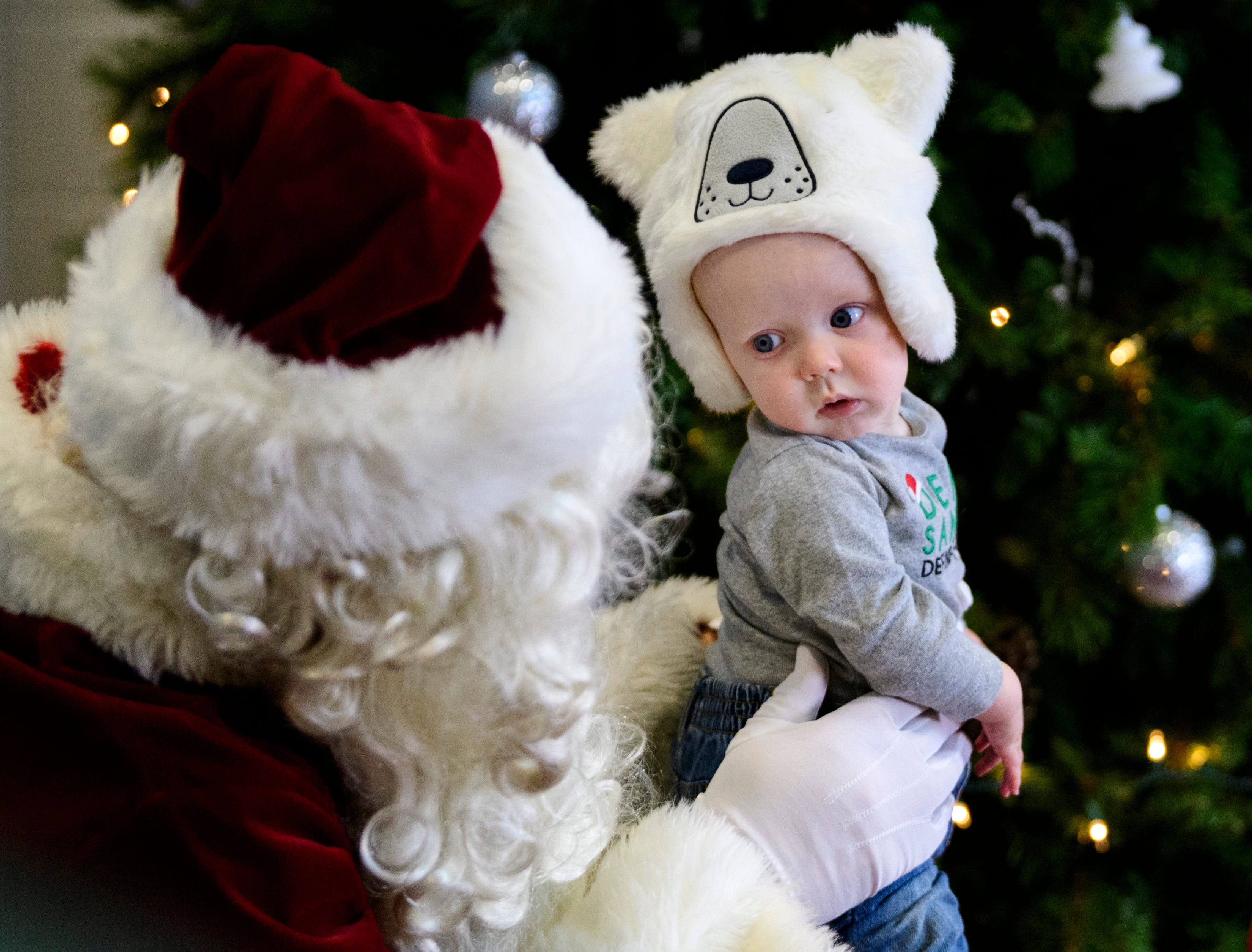 """Seven-month-old Xander Vaughn stares at Santa while they take a portrait alongside his brother Gabriel Vaughn, 3, not pictured, during the ninth annual """"Skating with Santa"""" event at Swonder Ice Arena in Evansville, Sunday evening, Dec. 16.  A portion the event's proceeds were donated to Autism Evansville, a local non-profit resource center for families with children on the autistic spectrum."""