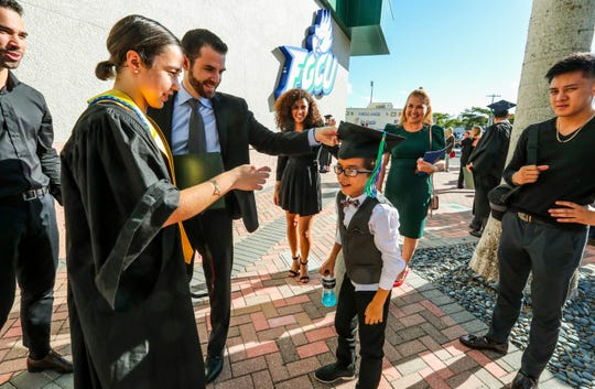 The family gets a laugh after Sissi's nephew, Anthony Lopez Camps, puts her cap on with the help from his father, Victor Inostroza Lopez, now of Dallas, TX. TheÊjourney Sissi Lopez Diaz Jensen took that culminated in her walking across the stage for FGCU's fall commencement at Alico Arena on Sunday, diploma in hand, has been aÊlong one. That journey that started in Cuba, with a stop in Denmark, and brought her toÊthe United States at age 7 is what prompted her to focus her studies on political science and look to the future andÊpursueÊa career in law, and a dedication to public service.