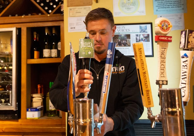 Jeff Buchanan pours drinks for guests while working in Trio in Greenville Wednesday, Dec. 12, 2018.
