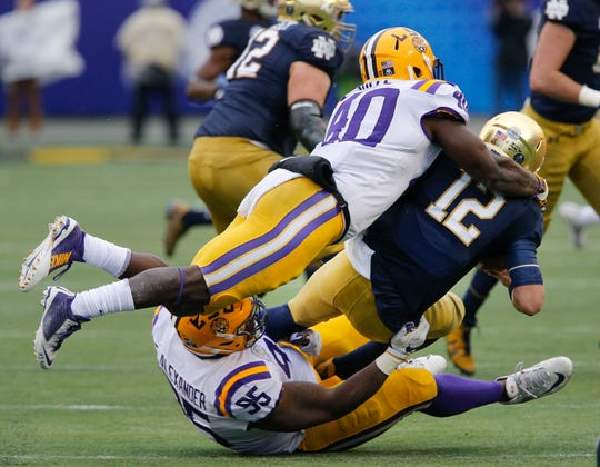 Jan 1, 2018; Orlando, FL, USA; Notre Dame Fighting Irish quarterback Ian Book (12) is sacked by LSU Tigers nose tackle Ed Alexander (95) and linebacker Devin White (40) during the second quarter in the 2018 Citrus Bowl at Camping World Stadium. Mandatory Credit: Reinhold Matay-USA TODAY Sports