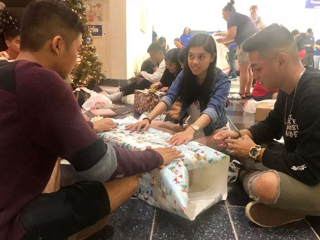 Karlmichael Pere, left, Andrea Gutierrez, 16, and Roan Carlos, 17, wrap up a toy gun and shoes at the Big Wrap on Sunday.