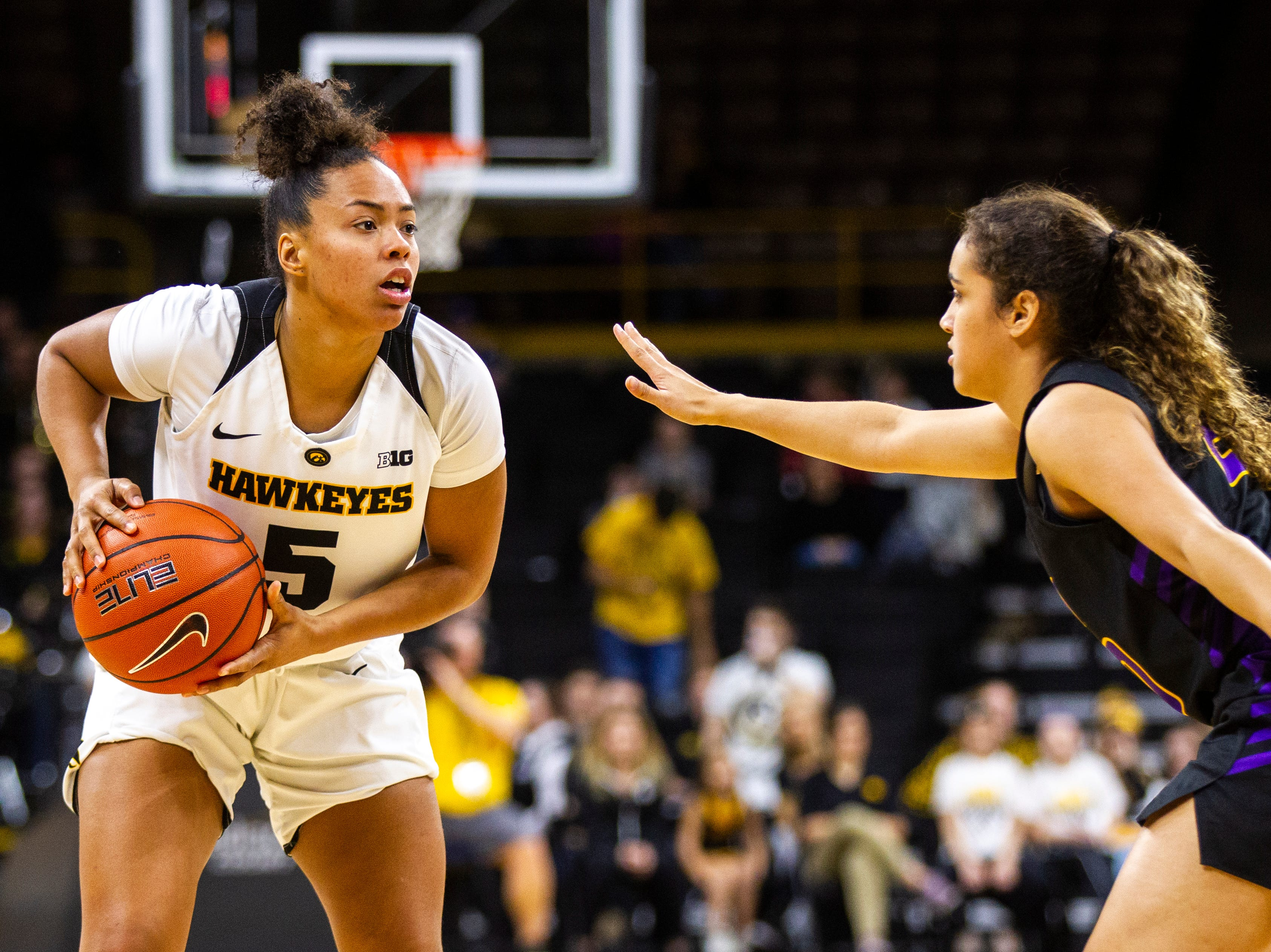 Iowa guard Alexis Sevillian (5) gets defended by Northern Iowa guard Alyssa Iverson (20) during a NCAA women's basketball game on Sunday, Dec. 16, 2018, at Carver-Hawkeye Arena in Iowa City.