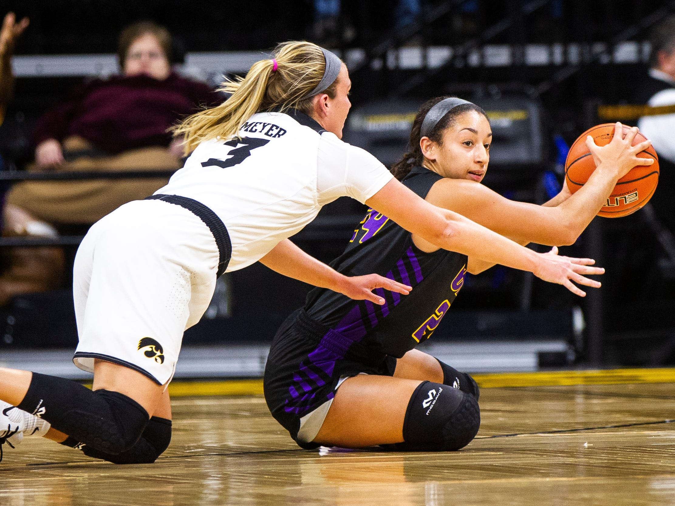 Northern Iowa guard Mikaela Morgan (24) attempts to recover a loose ball while Iowa guard Makenzie Meyer (3) dives in during a NCAA women's basketball game on Sunday, Dec. 16, 2018, at Carver-Hawkeye Arena in Iowa City.