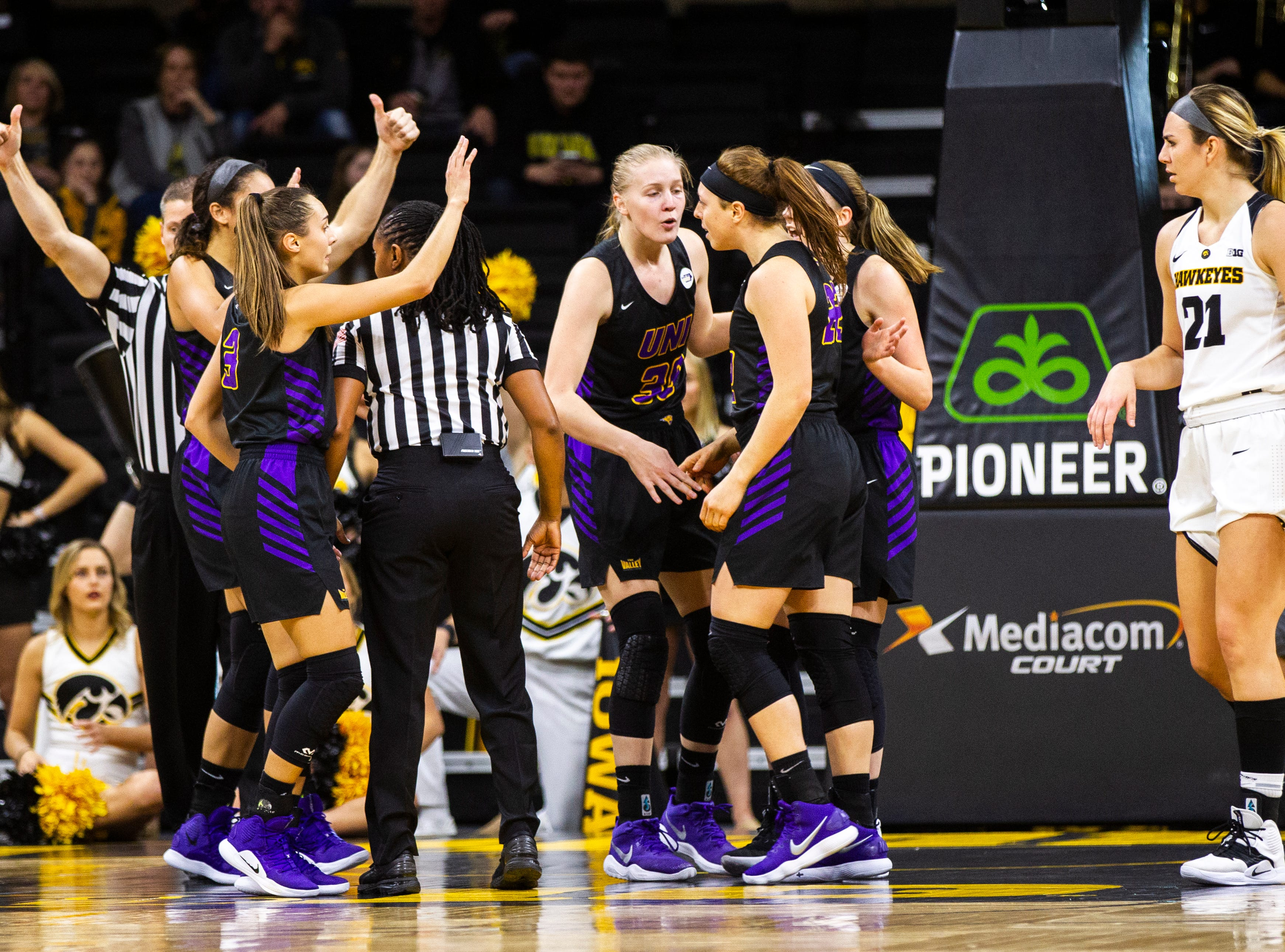 Northern Iowa guard Rose Simon-Ressler (22) is embraced by teammates after winning possession during a NCAA women's basketball game on Sunday, Dec. 16, 2018, at Carver-Hawkeye Arena in Iowa City.