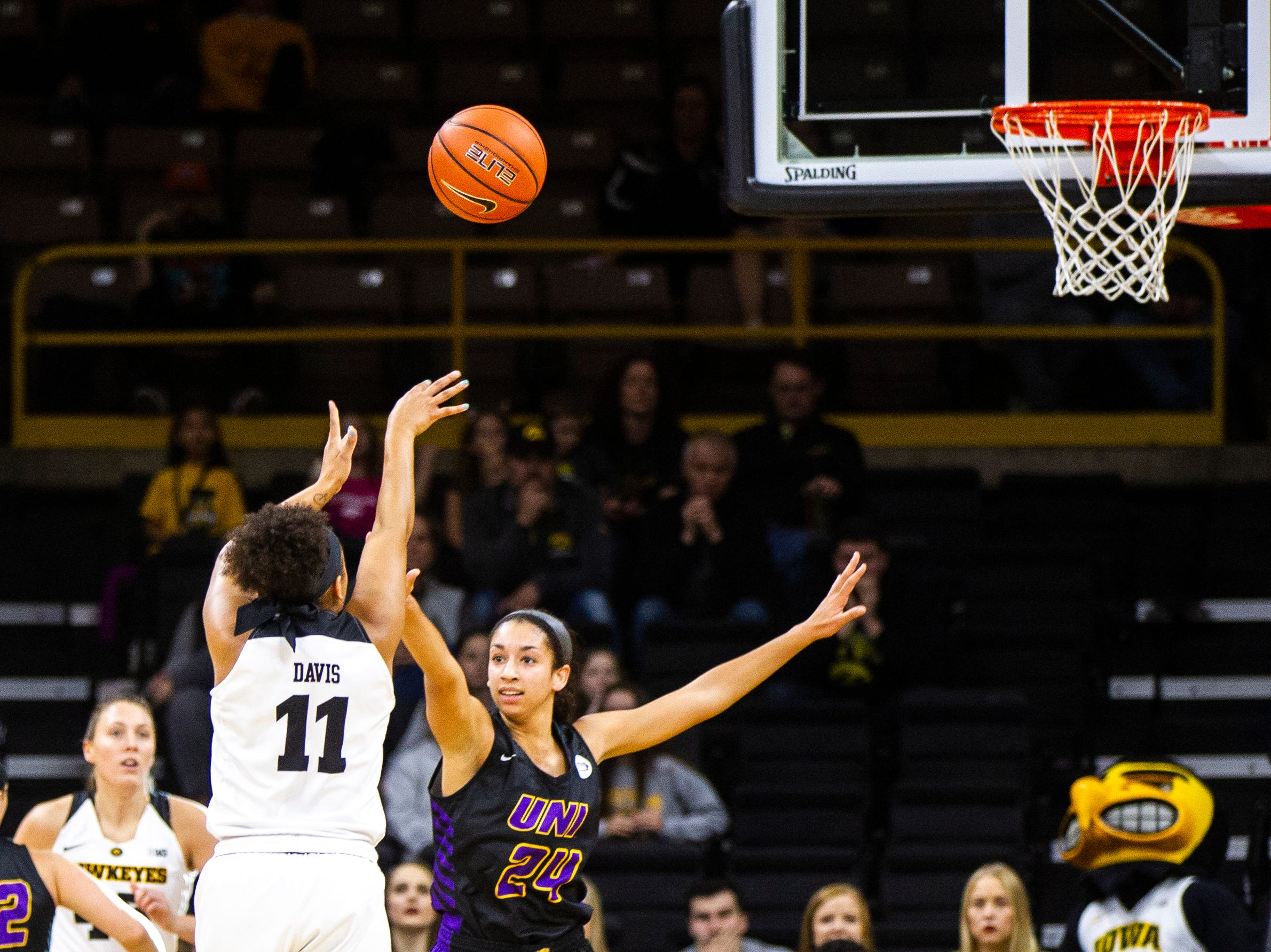 Iowa guard Tania Davis (11) shoots a 3-point basket while being defended by Northern Iowa guard Mikaela Morgan (24) during a NCAA women's basketball game on Sunday, Dec. 16, 2018, at Carver-Hawkeye Arena in Iowa City.