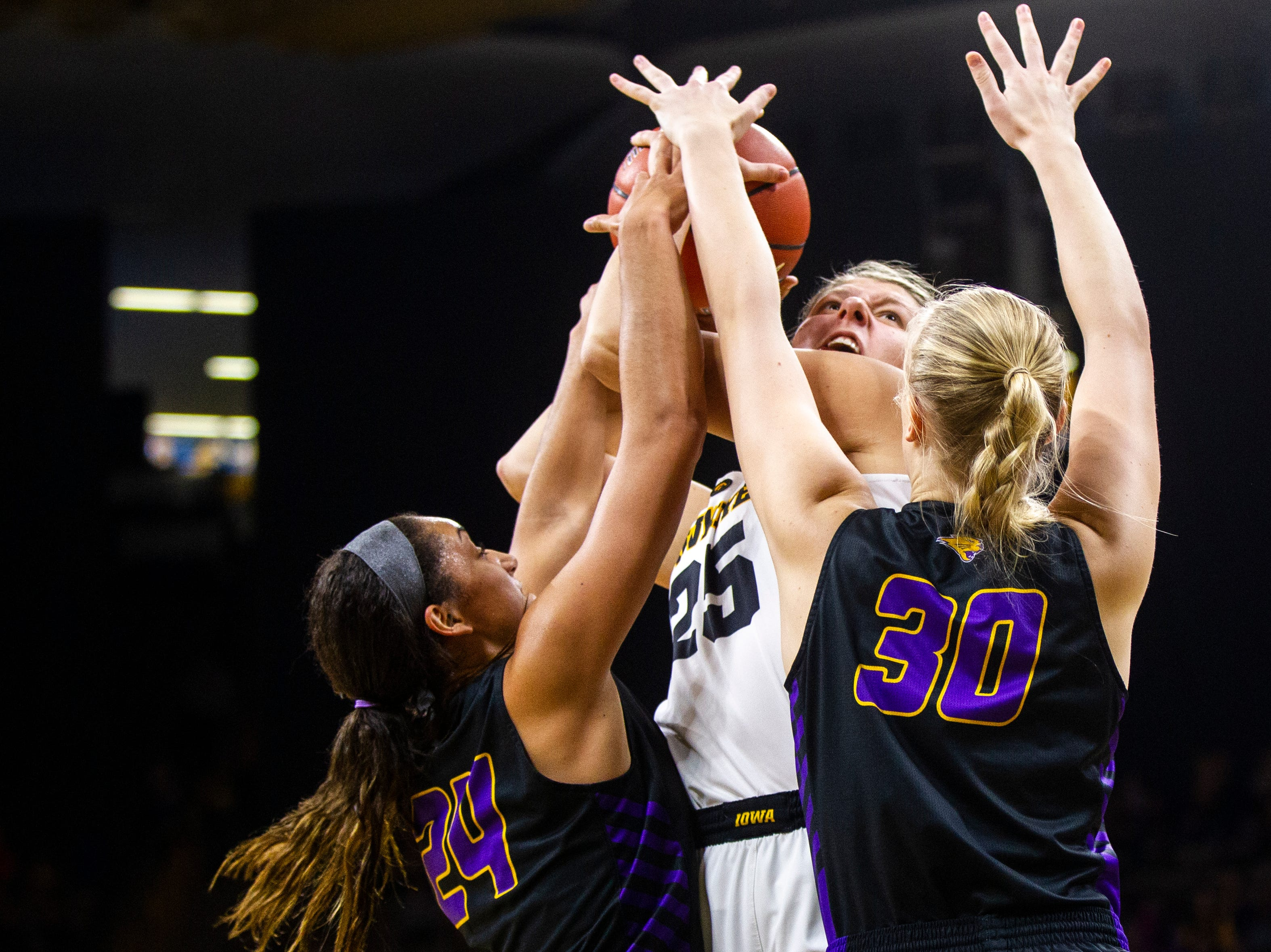 Iowa's Monika Czinano (25) gets defended by Northern Iowa guard Mikaela Morgan (24) and center Cynthia Wolf (30) during a NCAA women's basketball game on Sunday, Dec. 16, 2018, at Carver-Hawkeye Arena in Iowa City.