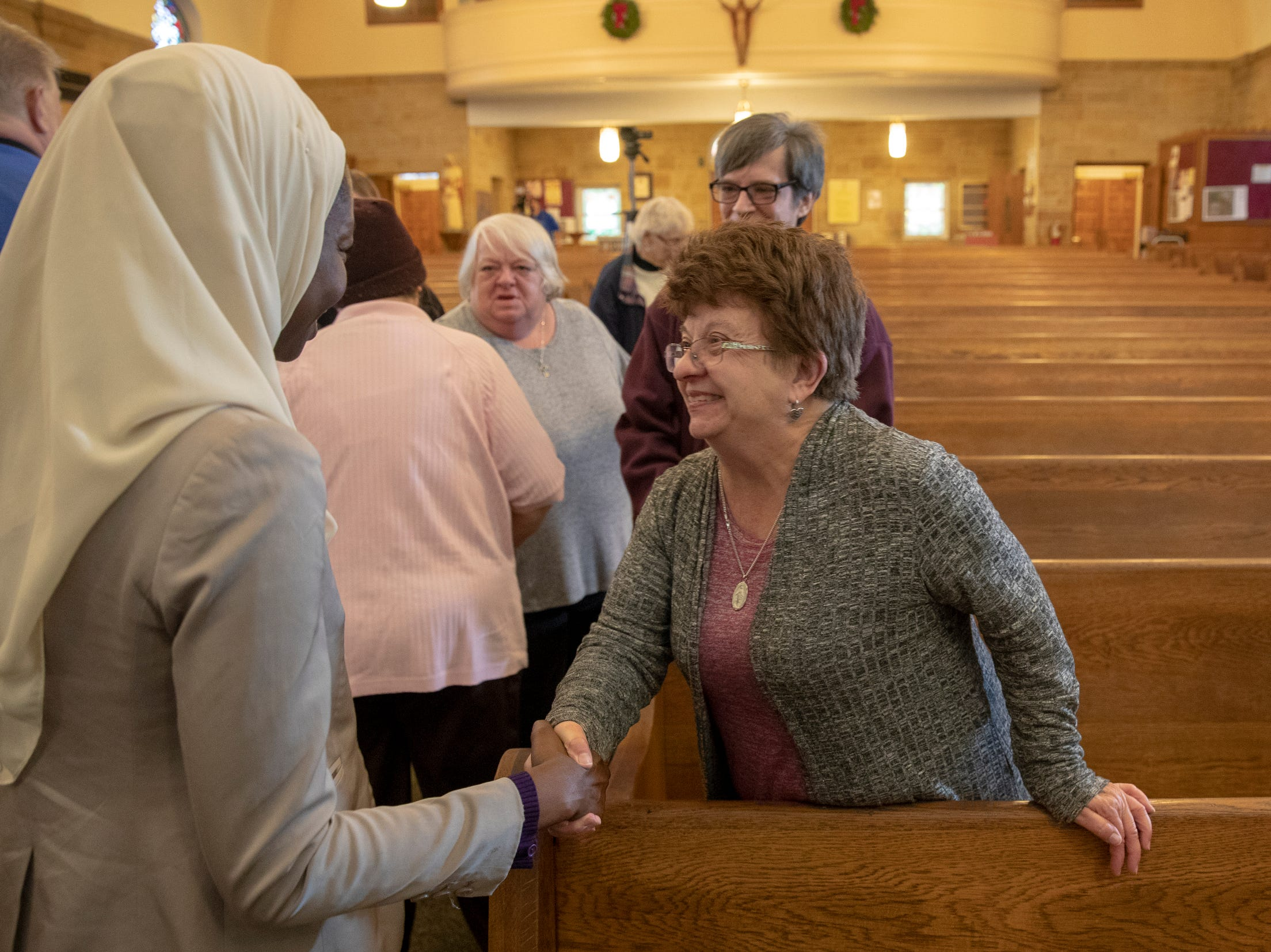 Halima Al-Khattab (left), embraces Mary Kendall, during a Christian-Muslim prayer service at Saint Philip Neri Catholic Church, Indianapolis, Sunday, Dec. 16, 2018. The service is the second annual, and joins people from this church and Indianapolis' Masjid Al-Fajr.